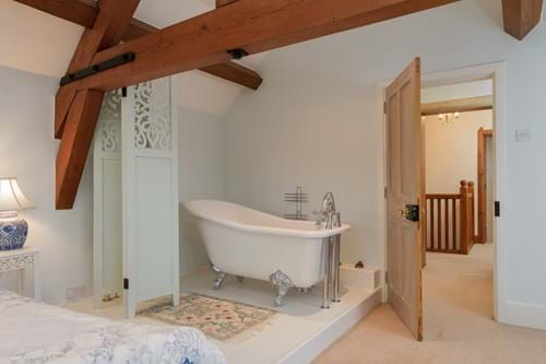 a bedroom with a free-standing bath in a period house for sale near Chester