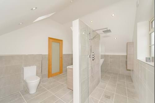 a contemporary en suite bathroom with a walk through shower