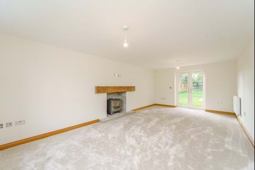 A sitting room with a log burner and french windows in a house for sale in Bunbury