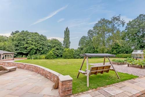 the garden with wooden hammock seat of a barn conversion for sale in Tattenhall