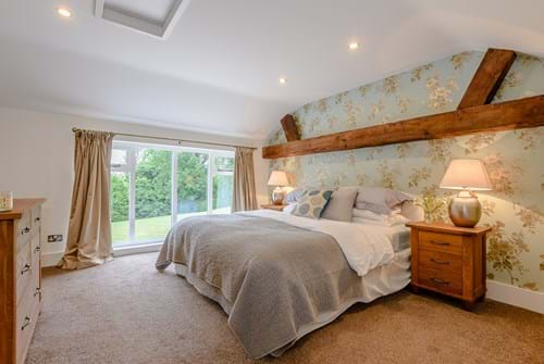 a bedroom with character beams in a barn conversion for sale in Tattenhall