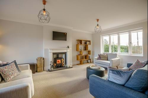 the living room in a modern house for sale.  Contemporary styling and with a log burning stove