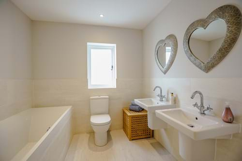a contemporary bathroom with stone coloured tiles and white sanitary wear in a house for sale in Churton