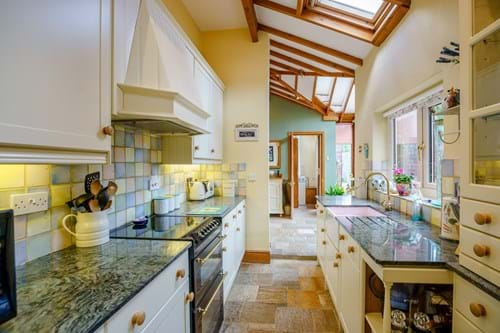 Kitchen with cream units and granite work surfaces in a house for sale in Huxley near Chester