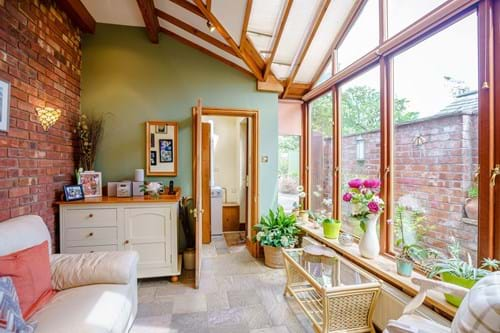 Garden room with a confy sofa and chair in a terraced house for sale with Chester estate agency Rickitt Partnership