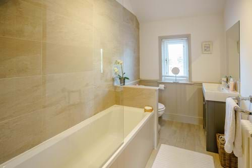 contemporary bathroom wih sand coloured tiles and tongue and groove detailing on the walls in a house for sale with Chester estate agents Rickitt Partnership