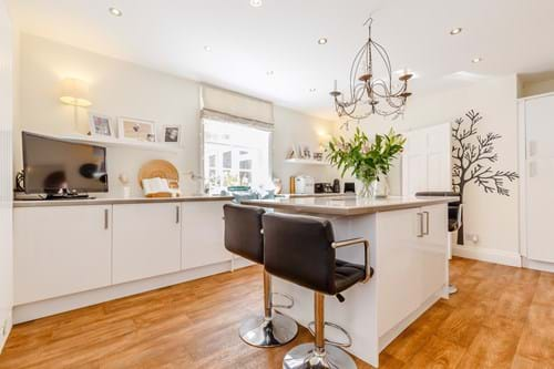 A contemporary kitchen with white units and an island in a house for sale with Chester estate agents Rickitt Partnership