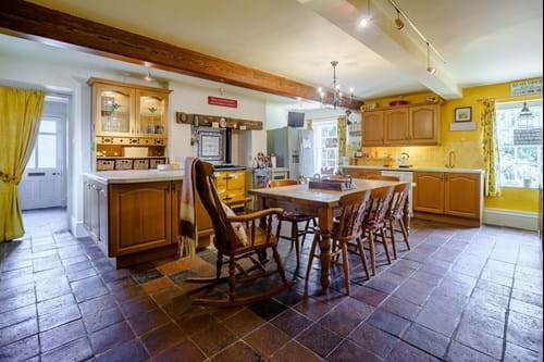a farmhouse style kicthen with tiled floor and yellow range cooker in a house for sale with estate agent in Chester Rickitt Partnership