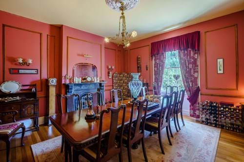 a dining room in a period house with red painted walls, wooden floor, a marble fireplace and sash window